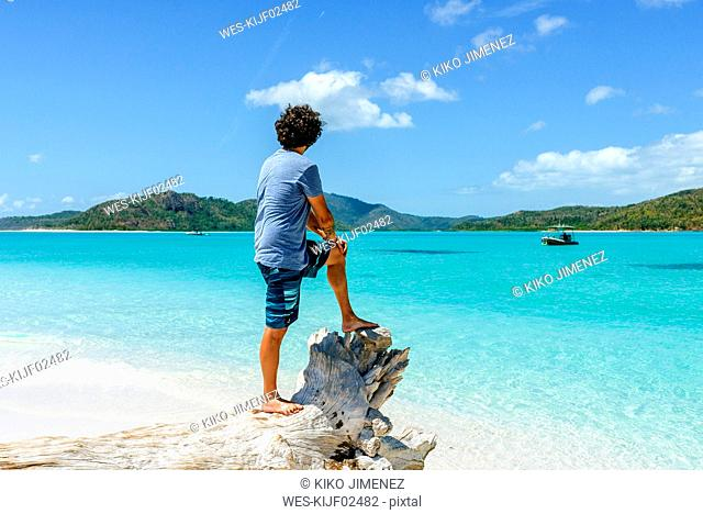 Australia, Queensland, Whitsunday Island, man standing on log at Whitehaven Beach