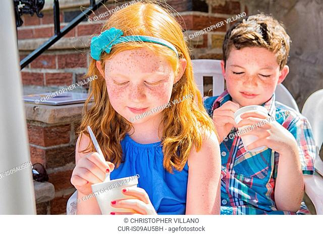 Brother and sister concentrating whilst eating ice cream