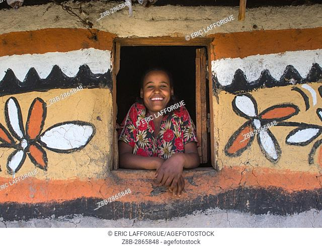 Ethiopian woman standing in the window of her traditional painted house, Kembata, Alaba Kuito, Ethiopia