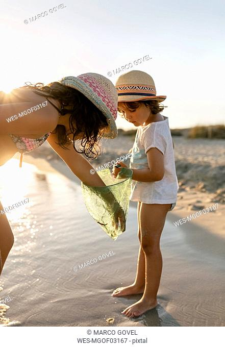 Spain, Menorca, two girls with dip net on the beach