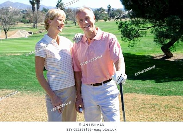 Mature couple standing on golf course, playing golf, woman leaning on man&#xe2 &#x20ac &#x2122 s shoulder, smiling, portrait