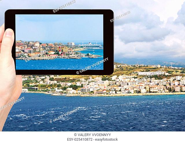 travel concept - tourist snapping photo of town Reggio di Calabria from Strait of Messina, Calabria, Italy on tablet pc