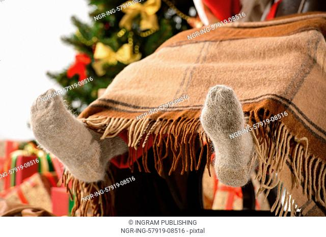 Santa sitting in rocking chair near christmas tree and warming his feet near fireplace. Closeup of Santa's feet in wool socks