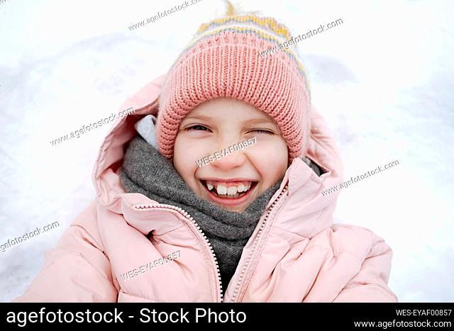 Portrait of happy girl lying on snow