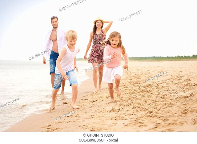 Family running along sandy beach