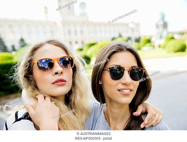 Austria, Vienna, two young women embracing with Museum of Art History in background