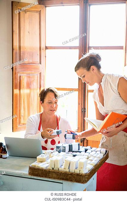 Female business owner checking quality of soap bars in handmade soap workshop office