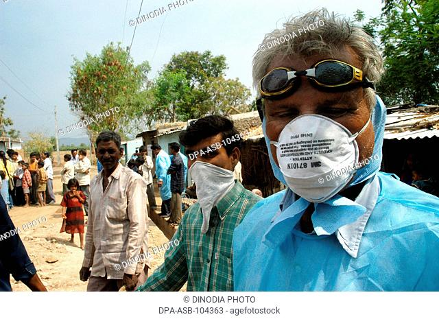 Health workers cover their faces with protective masks as the go house to house to cull infected chickens in the backyard of the villager's houses at Hingona...
