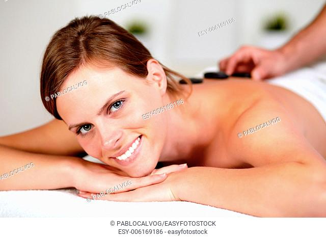 Close up portrait of a relaxed girl receiving a hot stone massage at spa, looking at you