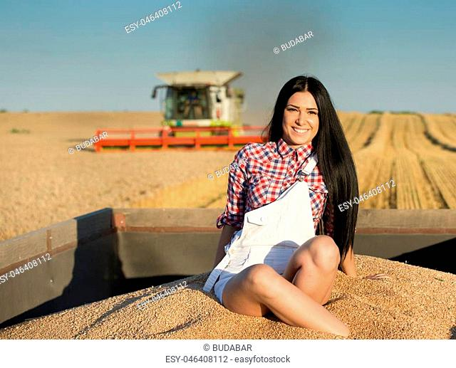 Beautiful young woman sitting in tractor trailer full of wheat grains during harvest on the field