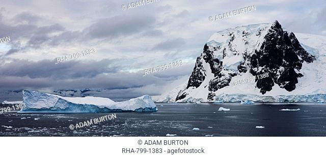 Huge tabular iceberg drifting past mountain range on the Antarctic Peninsula, Antarctica, Polar Regions