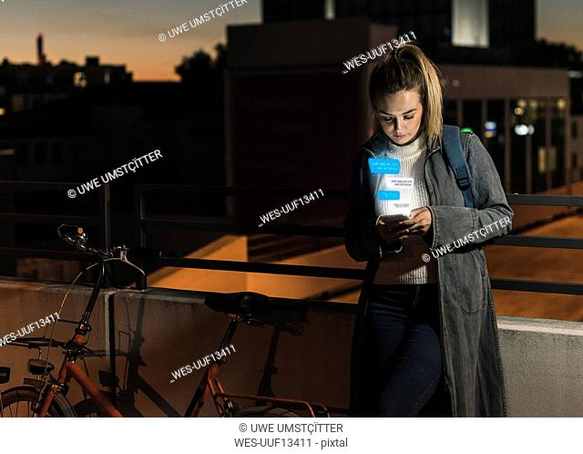 Young woman outdoors at night with text emerging from smartphone