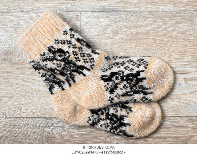Pair of wool socks against wood background