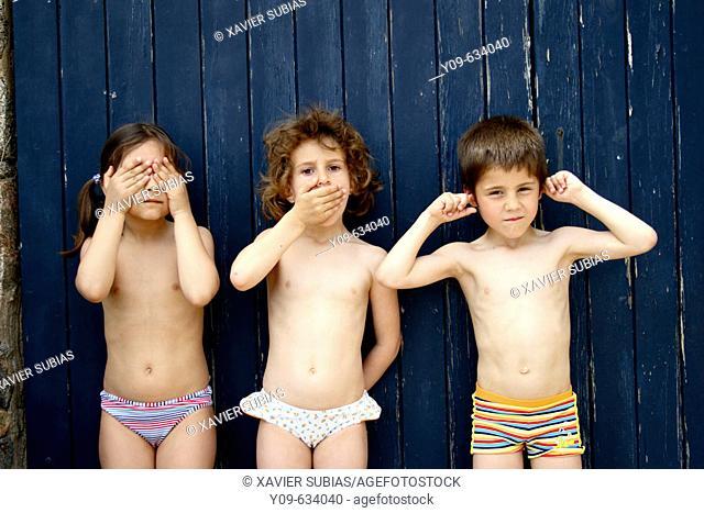Three children as three wise monkeys