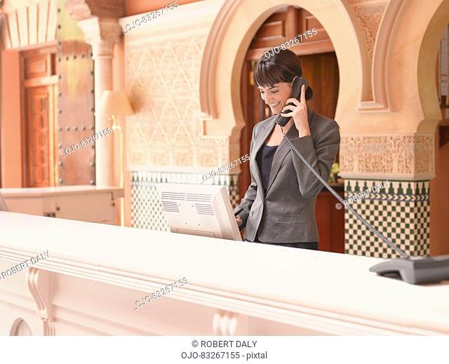 Hotel receptionist talking on telephone