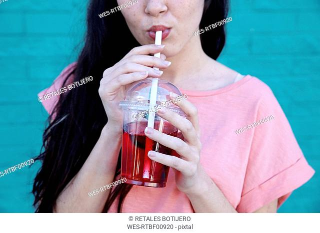 Young woman drinking soft drink, partial view