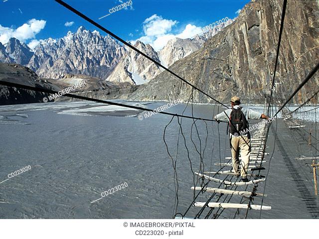 Man crossing suspension bridge, Karakorum, Pakistan