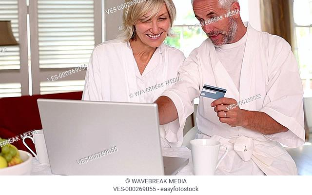 Happy couple shopping online in bathrobes