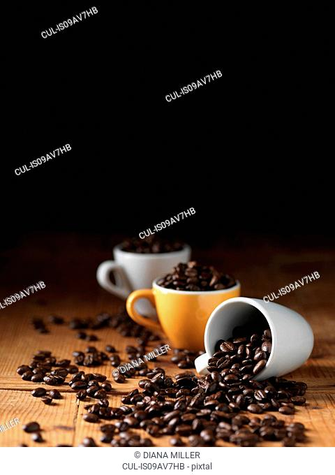Coffee beans in espresso cups spilling onto wooden table