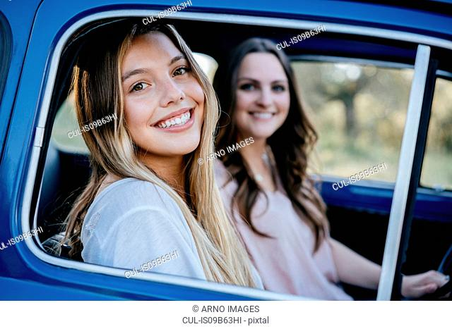 Friends in vintage car looking at camera smiling, Firenze, Toscana, Italy, Europe