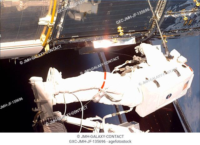 Astronaut C. Michael Foale, standing on the end of Discovery's remote manipulator system (RMS), which had hoisted him to a task station on the Hubble Space...