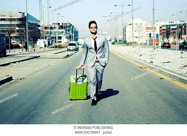 Man dressed in suit and suitcase in the street