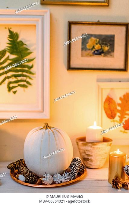 Console table, detail, autumnal decoration, candles, picture frames, leaves, pumpkin