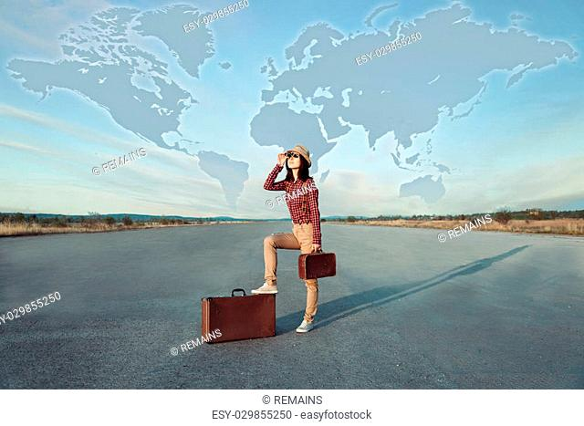 Traveler woman with suitcase looks on road. World map in the sky