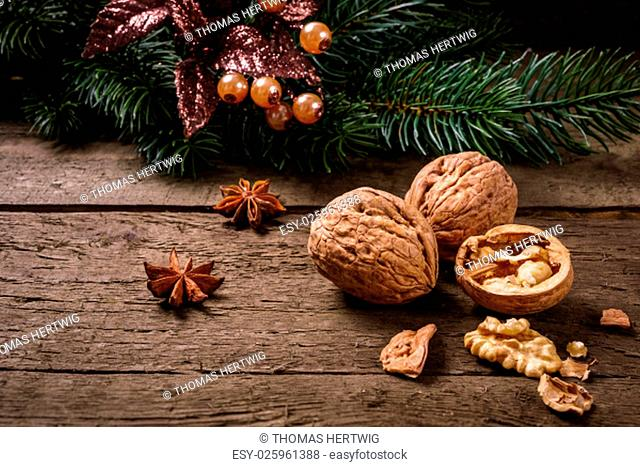 Anise, fir branch, cranberries and walnuts on wooden planks. You can use it for christmas background, card or voucher