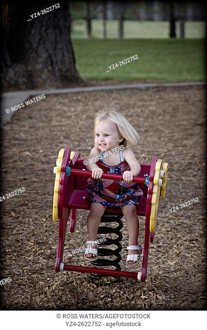 A female toddler plays on a toy at a park in Spokane, Washington, USA