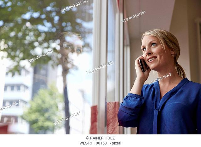 Businesswoman standing by window, talking on the phone