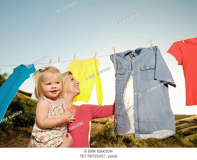 Mother with daughter 12-17 months hanging laundry on clothesline