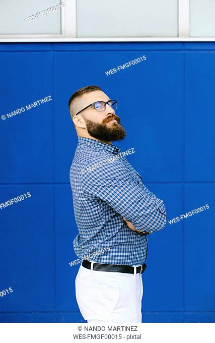 Portrait of bearded hipster businessman wearing plaid shirt standing in front of blue background