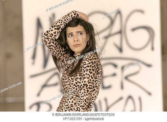 portrait of scared defiant humorous woman ruffling hair, curling lips, pout, wearing fashionable leopard print sweater, confused, in Munich, Germany