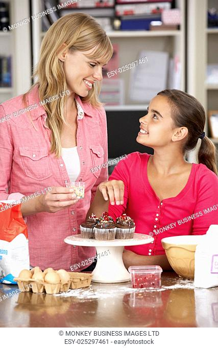 Mother And Daughter Decorating Homemade Cupcakes In Kitchen