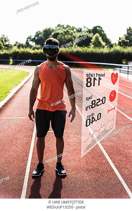 Athlete on tartan track wearing VR glasses surrounded by data