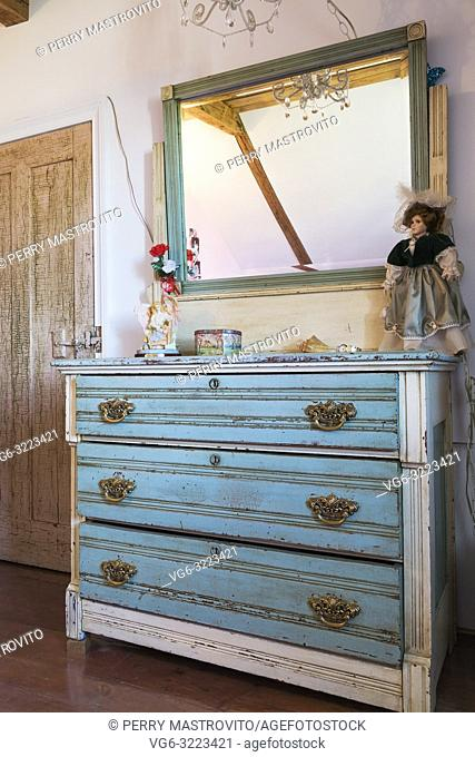 Child's bedroom with blue teal antique reproduction dresser on upper floor inside an old 1835 fieldstone house