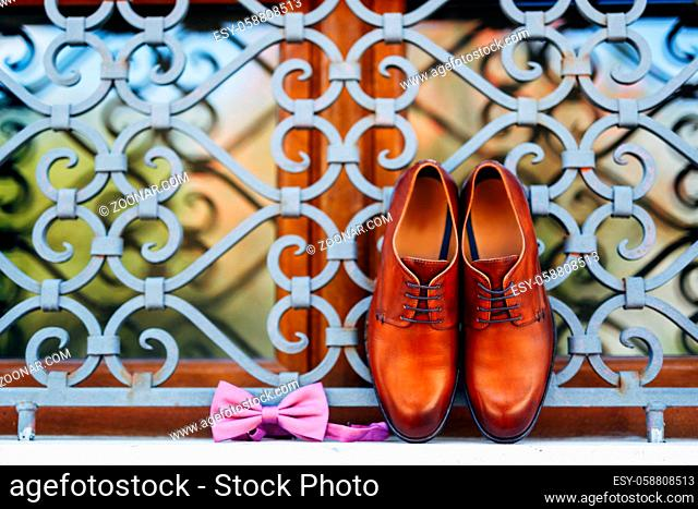New brown men's shoes and a bow tie with an untied ribbon on the window at the metal grille outside. High quality photo