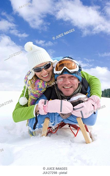 Couple laying on sled in snow together