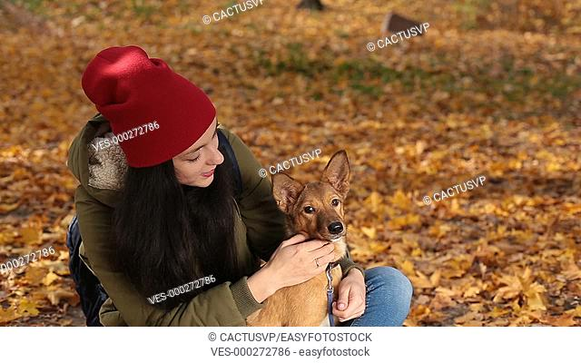 Portrait of girl with lovely dog in yellow foliage