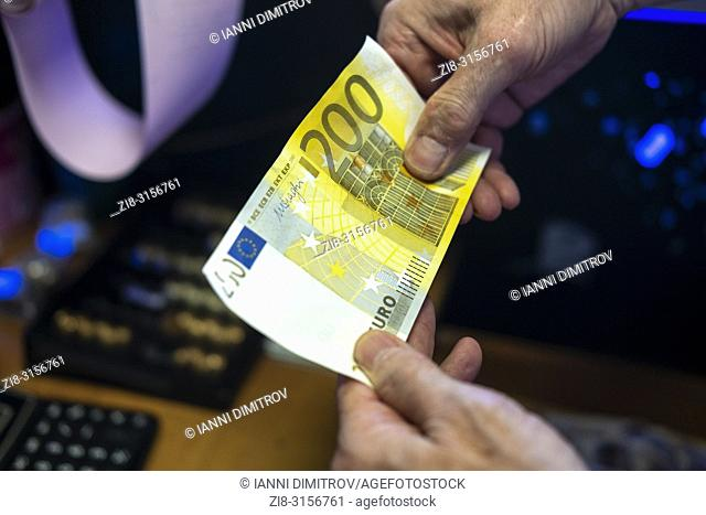 Cash payment- person checks two hundred euro banknote unde UV light-close-up