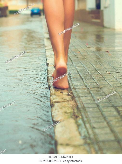 Woman having fun on the street after the rain