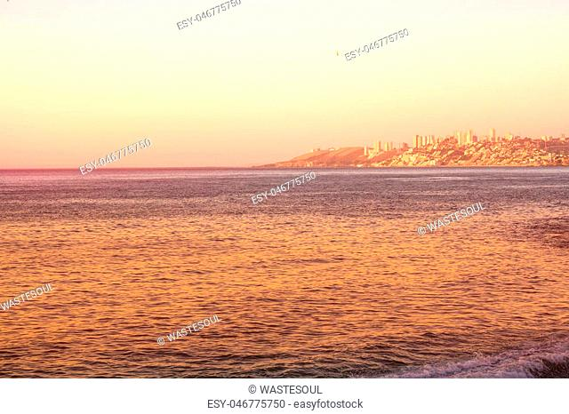 Pacific ocean at the evening with buildings of Vina del Mar, Chile in the distance