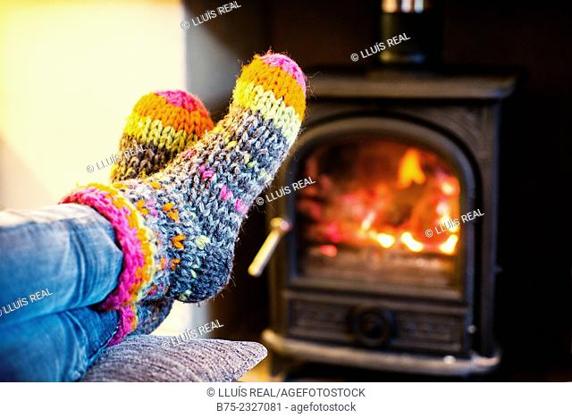Feet warming up with a hand made colored socks in a position of rest and relax near a wood stove in winter
