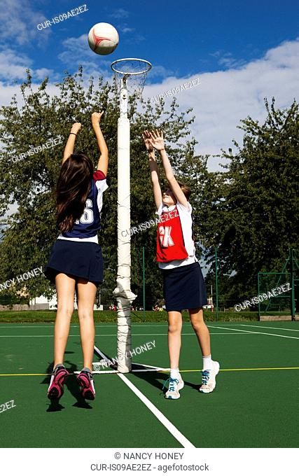 Two schoolgirls playing netball
