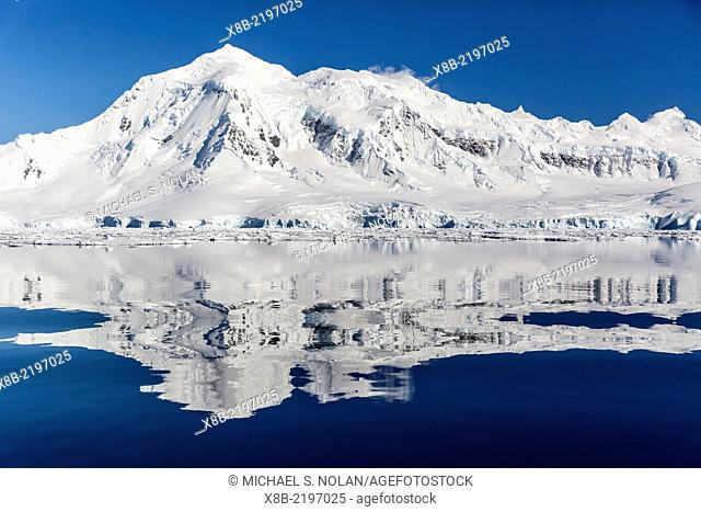 Snow-capped mountains reflected in the Neumayer Channel near Port Lockroy, Antarctica