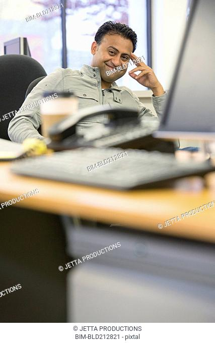 Asian businessman smiling at desk in office