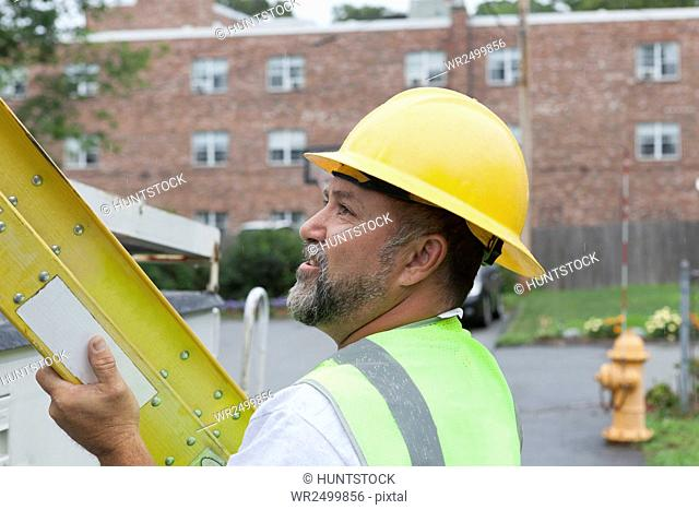 Utility worker preparing a ladder for work at site