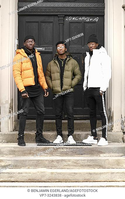 three stylish male friends standing on stairs in front of door, in city Munich, Germany