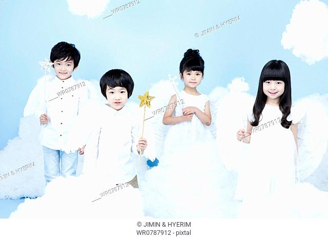 four kids with looks of angels on the clouds